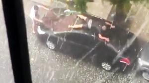 Man Desperately Tries to Protect Car From Hail