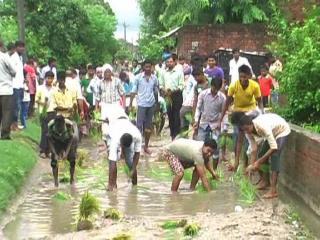 टूटी सड़कों से परेशान किसानों ने सड़क पर ही की धान की रोपाई