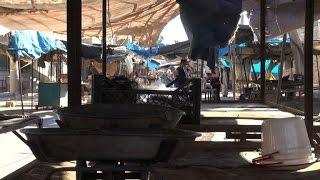 Under fresh siege, shoppers in east Aleppo scour meagre markets