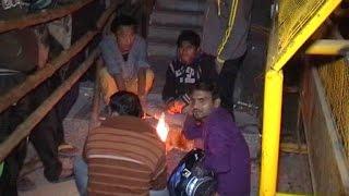 दिल्ली : बैंकों के बाहर खड़े लोग आग जलाकर इंतजार करने को मजबूर
