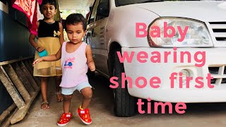 Baby wears shoe for first time -