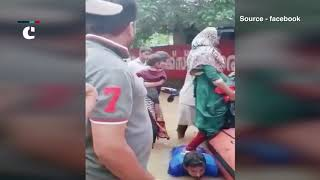 Kerala Floods: Salute! Man bent down on his knees in flooded water to held women get on rescue boat