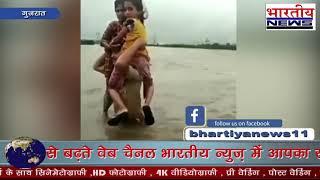 गुजरात में बाढ़ पीडिता बच्चियों को अपने कंधे पर लेकर जाता पुलिस का जवान जन सेवा का फर्ज निभाती खाकी।