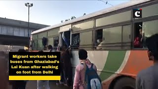 Migrant workers take buses from Ghaziabad's Lal Kuan after walking on foot from Delhi