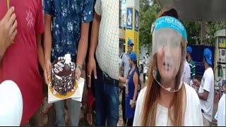 Pratima feeds cake to man masked as Modi at Fuel hike protest