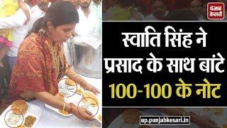 स्वाति सिंह ने प्रसाद के साथ बांटे 100-100 के नोट